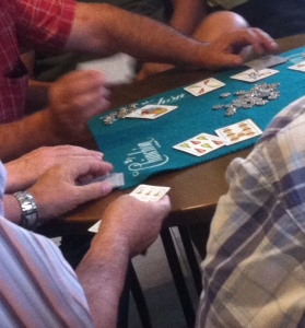 Old men playing a loud, liquor-fueled game of cards in a local bar.